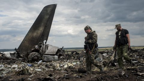 Pro-Russian fighters walk past the wreckage of the downed aircraft.