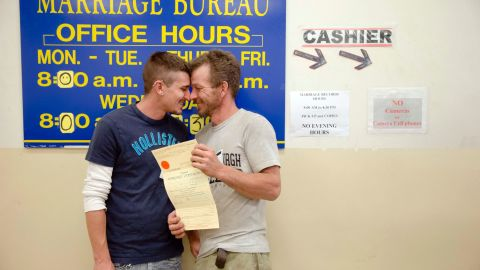 William Roletter, left, and Paul Rowe get close after having their photo taken with their marriage certificate May 21, 2014, at Philadelphia City Hall.