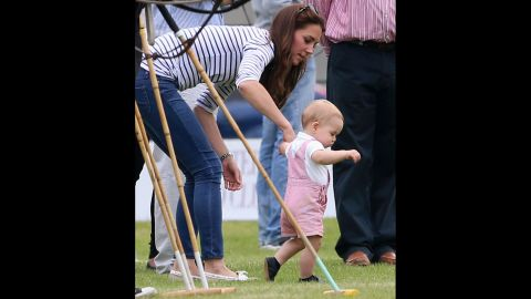 Prince George of Cambridge takes his first steps in public as his mother Catherine, Duchess of Cambridge, holds his hand on Sunday, June 15, in Cirencester, England.