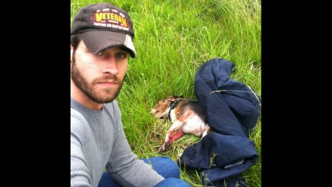 """Aaron Schneider, an Iraq War veteran, snapped this shot after he rescued a beagle that he saw get hit by a car on Interstate 470 in Lee's Summit, Missouri. Schneider crossed several lanes of traffic to get the dog to safety, and he later took it to get medical care, <a href=""""http://www.kmbc.com/news/iraq-war-veteran-saves-dog-hit-by-car-along-i470/26484176#!0c192"""" target=""""_blank"""" target=""""_blank"""">according to KMBC.</a> The dog was expected to recover from its injuries."""