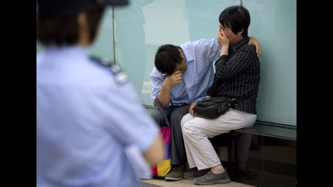 A police officer watches a couple cry outside the airline's office building in Beijing after officials refused to meet with them on June 11, 2014. The couple's son was on the plane.