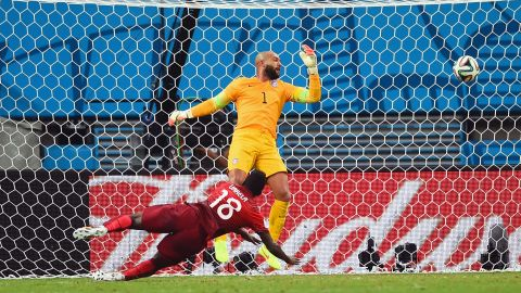 Silvestre Varela of Portugal scores his team's second goal as goalkeeper Tim Howard of the United States looks on.