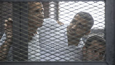 Peter Greste, from left, Mohamed Fahmy and Baher Mohamed are held in a cage during their trial in 2014.