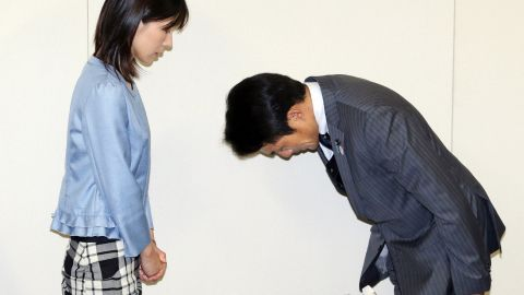 Akihiro Suzuki bows to Ayaka Shiomura, a fellow assembly member, to apologize for his sexist jeer during a Tokyo city hall event.