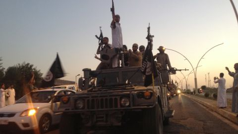 In this photo taken Monday, June 23, 2014, fighters of the al-Qaida-inspired Islamic State of Iraq and the Levant (ISIL) parade in a commandeered Iraqi security forces armored vehicle down a main road at the northern city of Mosul, Iraq.