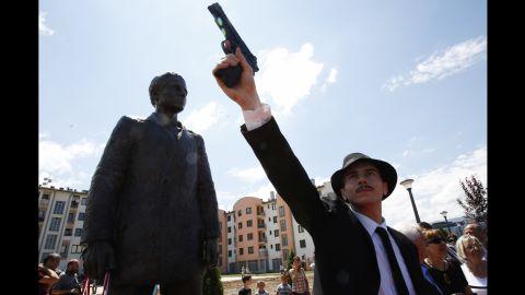 Bosnian actor Jovan Mojsilovic poses with a plastic gun replica at the unveiling of a statue of Gavrilo Princip in Sarajevo, June 27.