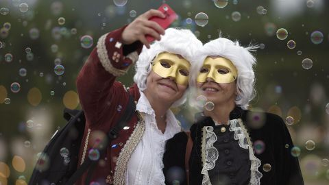 Guests dressed in period costumes pose for a selfie Saturday, June 28, at a ball held in the gardens of the Palace of Versailles in Versailles, France.