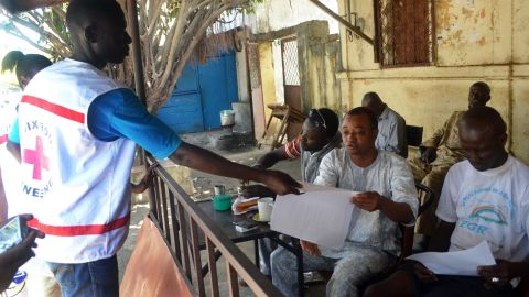 Members of the Guinean Red Cross distribute information leaflets during an awareness campaign on the Ebola virus on April 11, 2014 in Conakry. Guinea.