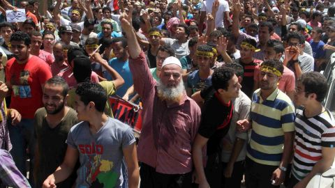 """Egyptian supporters of the Muslim Brotherhood movement shout slogans during a rally to mark the first anniversary of the military ouster of president Mohamed Morsi on July 3, 2014 in Cairo's Mattarya district. Egyptian police swiftly quashed Islamist protests firing tear gas and arresting dozens of demonstrators, as the protests are seen as a test of the Islamists' strength, with the Muslim Brotherhood-led Anti Coup Alliance having issued an aggressive rallying cry demanding a """"day of anger"""" to mark Morsi's overthrow. AFP PHOTO / KHALED KAMEL"""