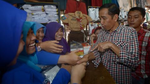 """Presidential candidate Joko """"Jokowi"""" Widodo visits a traditional market during his campaign in Jakarta on June 30. Known for his folksy and humble demeanor, Widodo symbolizes a new breed of leadership to his admirers."""