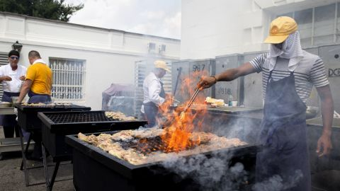 In close to 100-degree heat, Kashif Browne shields his face with a towel Wednesday, July 2, as he grills chicken in preparation for the White House's July Fourth activities.