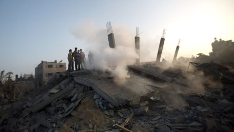 Palestinians inspect damaged houes after an Israeli missile strike hit Gaza City on July 8, 2014 . The Israeli air force launched dozens of raids on the Gaza Strip overnight after massive rocket fire from the enclave pounded southern Israel, leaving 17 people injured, sources said. AFP PHOTO / MAHMUD HAMS (Photo credit should read MAHMUD HAMS/AFP/Getty Images)