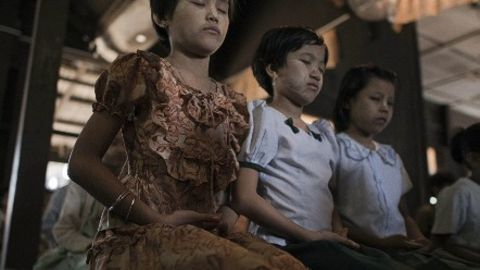 Girls meditating at a Buddhist monastic school in Myanmar.