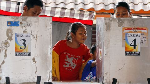 Children wait for their parents who vote in the presidential election in Bali on July 9. As the world's third-largest democracy held an election for a new president.
