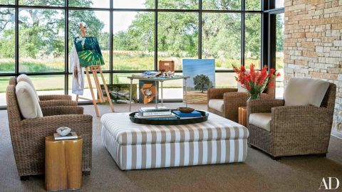 """Breezeway: Mr. Bush sometimes paints at an easel in the enclosed breezeway, where the windows are replaced with screens in warm weather; the ottoman and the cushions on the sea-grass chairs are covered in Sunbrella fabrics. <a href=""""http://www.architecturaldigest.com/celebrity-homes/2014/laura-and-george-w-bush-prairie-chapel-ranch-texas-article?mbid=synd_cnn"""" target=""""_blank"""" target=""""_blank"""">See more at ArchDigest.com</a>"""