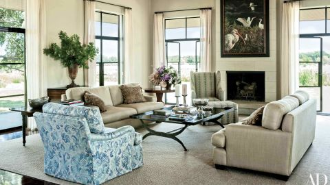 """Living Room: Mounted on the living area's limestone chimney breast is an Adrian Martinez painting, which over looks sofas clad in a Glant fabric, a club chair upholstered in a Groves Bros. print, and a cocktail table designed by Mrs. Bush; the windows are curtained in a Calvin Fabrics linen, and the ammonite fossils displayed atop the pedestal table were found on the property. <a href=""""http://www.architecturaldigest.com/celebrity-homes/2014/laura-and-george-w-bush-prairie-chapel-ranch-texas-article?mbid=synd_cnn"""" target=""""_blank"""" target=""""_blank"""">See more at ArchDigest.com</a>"""