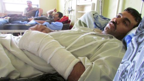 Ali Hassan, 28, lies in a hospital bed in Baghdad. Hassan was shot in the leg and the hand by a sniper during a firefight Wednesday, July 9, in Ramadi in the Anbar province.