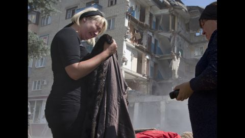 Eugenia Gubareva cries on July 10 after finding clothes belonging to her parents, who were killed during a bomb shelling in Mikolaivka, Ukraine.