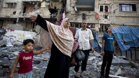 A Palestinian family leaves its house after it was damaged in an Israeli air strike on July 10, 2014 in Gaza City. The Israeli air force overnight hit more than 300 Hamas targets in the Gaza Strip in response to rocket fire from the besieged Palestinian territory, an army spokesman said. AFP PHOTO / MOHAMMED ABEDMOHAMMED ABED/AFP/Getty Images