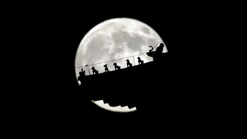 The moon rises behind figurines on a pavilillon in Beijing, China. Due to it's closer proximity to the Earth the moon appears larger and brighter than normal.