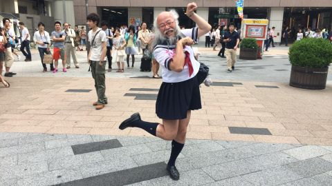 """Hideaki Kobayashi, 51, strikes his signature """"cat"""" pose outside Akihabara station in Tokyo on Sunday July 13.  Underneath the Japanese schoolgirl facade, he is a patent-holding computer engineer and accomplished photographer."""