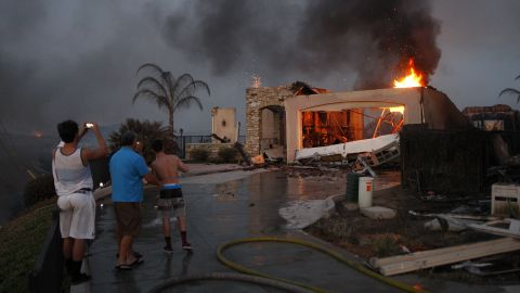 Residents photograph the burning ruins of their home, which was destroyed in a wildfire in Carlsbad, California, in May 2014.