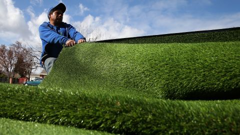 A worker installs an artificial lawn in front of an apartment building in San Jose in January 2014.