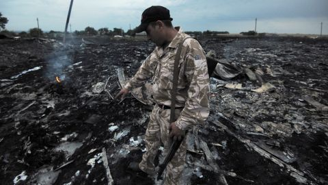 A man inspects debris from the plane.
