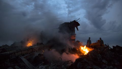 People walk amongst the debris at the crash site of a passenger plane near the village of Grabovo, Ukraine, Thursday, July 17. Ukraine said a passenger plane carrying 295 people was shot down Thursday as it flew over the country, and both the government and the pro-Russia separatists fighting in the region denied any responsibility for downing the plane.