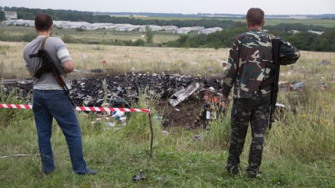 Pro-Russian rebels stand guard at the crash site.