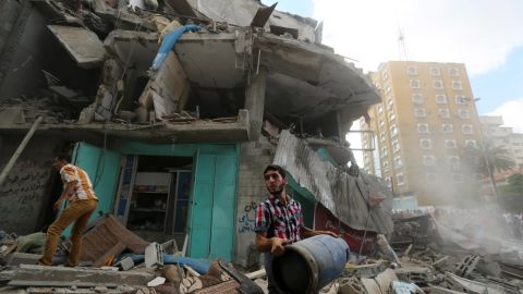 A Palestinian carries a gas cylinder salvaged from the rubble of an apartment building after it was hit by Israeli fire on July 18.