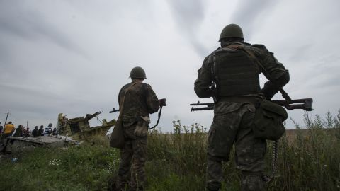 Pro-Russian rebels stand guard as the Organization for Security and Co-operation in Europe delegation arrives at the crash site on Friday, July 18, 2014.