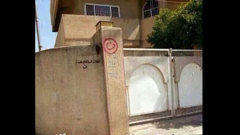 """A house in Mosul, Iraq, has the words """"property of ISIS"""" painted on a wall."""
