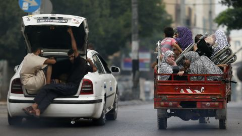 Palestinians flee their homes as Israeli troops focus their firepower on the Gaza town of Shaja'ia on Sunday, July 20. The shelling and bombing killed at least 60 people and wounded 300, according to the Gaza Health Ministry.