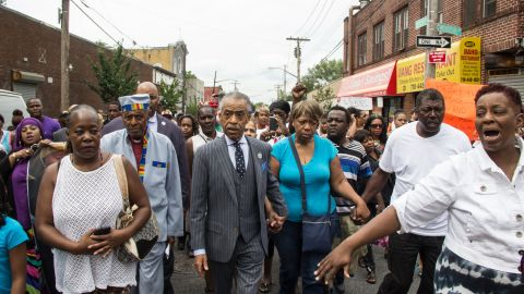 """People participate in a demonstration against the death of Eric Garner after he was taken into police custody in Staten Island.<a href=""""http://ireport.cnn.com/docs/DOC-1153998""""> Joel Graham</a> photographed the July 2014 demonstration, and captured this image of Garner's friends and family rallying alongside the Rev. Al Sharpton."""