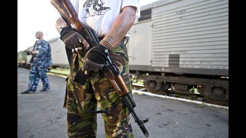 An armed pro-Russian rebel stands guard next to a refrigerated train loaded with bodies in Torez, Ukraine, on Sunday, July 20, 2014.