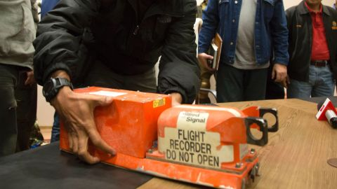 A Malaysian investigator takes a black box from Malaysia Airlines Flight 17 as it is handed over from Donetsk People's Republic officials to Malaysian representatives in the city of Donetsk, eastern Ukraine Tuesday, July 22, 2014. Bowing to international pressure Monday, pro-Moscow separatists released a train packed with bodies and handed over the black boxes from the downed Malaysia Airlines plane, four days after it plunged into rebel-held eastern Ukraine.