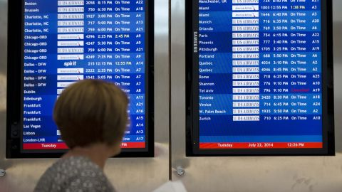 A woman in Philadelphia passes by a departure board that shows US Airways Flight 796, scheduled to fly to Tel Aviv, has been canceled on Tuesday, July 22. The Federal Aviation Administration told U.S. airlines they were temporarily prohibited from flying to the Tel Aviv airport after a Hamas rocket exploded nearby.