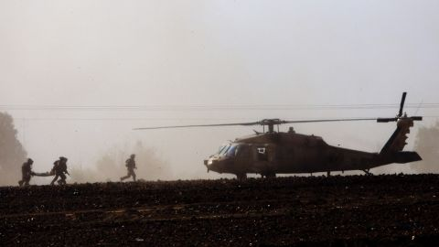 Israeli soldiers carry a wounded soldier to a helicopter near the Israel-Gaza border on July 24.