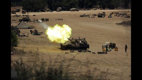 An Israeli tank fires toward Gaza from a position near Israel's border on July 24.