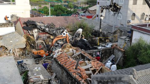 Rescue workers and firefighters search through the wreckage of TransAsia Airways flight GE222 after it crashed near the airport at Magong on the Penghu island chain on July 24, 2014. The domestic TransAsia Airways flight was carrying 54 passengers and four crew members when it crashed in the Penghu island chain, with 10 survivors. AFP PHOTO / Sam Yeh        (Photo credit should read )
