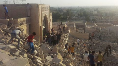 People walk on the rubble of the destroyed Mosque of The Prophet Younis, or Jonah, in Mosul, Iraq, on Thursday, July 24.