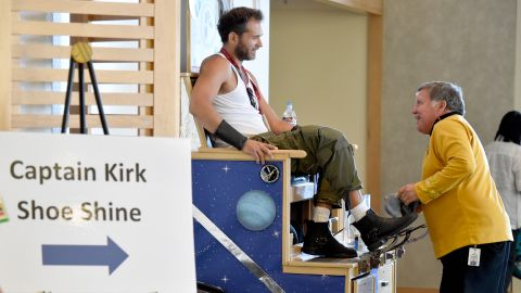 A man dressed as Wolverine gets his shoes shined by a costumed Captain Kirk on July 24.