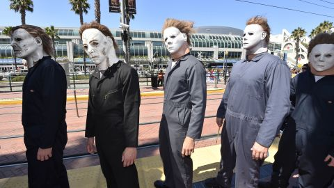 """People dressed as Michael Myers from the """"Halloween"""" films wait at a trolley stop outside of the San Diego Convention Center on July 24."""