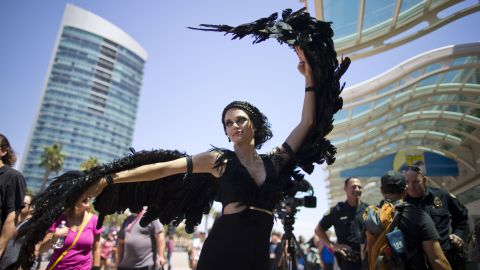 """A woman dressed as the character Katniss Everdeen from the movie """"The Hunger Games: Catching Fire"""" poses in front of Comic-Con on July 24."""