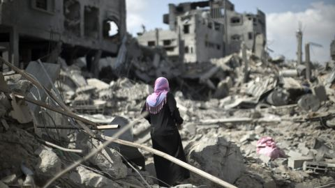 Caption:A Palestinian woman looks at the rubble of destroyed buildings and homes in the Shejaiya residential district of Gaza City on July 26, 2014. The bodies of at least 35 Palestinians were recovered from rubble across Gaza in the three hours since a humanitarian truce came into effect, raising to over 900 the overall death toll of Israel's onslaught on the territory since July 8, medics said. Thirteen bodies were recovered in Shejaiya in eastern Gaza City, 13 more in Deir al-Balah and Nusseirat in central Gaza, and nine in north Gaza. AFP PHOTO/MAHMUD HAMS (Photo credit should read MAHMUD HAMS/AFP/Getty Images)