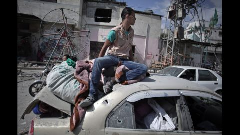 During a 12-hour cease-fire in Gaza City's Shijaiyah neighborhood on Saturday, July 26, a Palestinian man sits atop a car filled with belongings that were salvaged from a destroyed home.