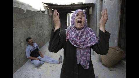 As her brother-in-law Mazen Keferna weeps on the ground, Manal Keferna cries upon discovering her family home destroyed by airstrikes in Beit Hanoun on July 26.