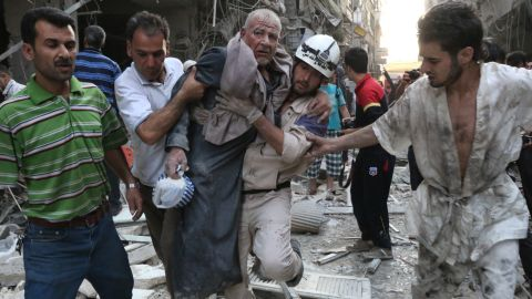 People carry an injured man away from the site of an airstrike, reportedly carried out by Syrian govern