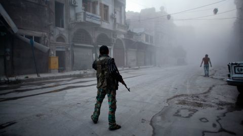 A rebel fighter stands on a dust-covered street in Aleppo on Monday, July 21.